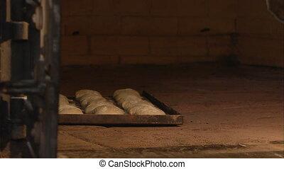 Putting dough in an oven - A medium shot of round doughs...