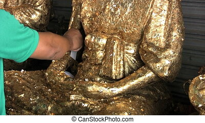 Putting Gold Leaf On Buddha Statue