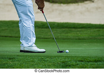 putting golf - Male golfer putting a golf ball in to hole.