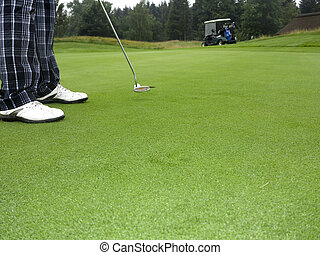 Golfer is putting on the green towards hole with buggy in background.