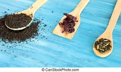 Putting herbal tea leaves in wooden spoons on blue...