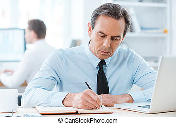 Putting his ideas on paper. Serious businessman in formalwear writing in note pad while sitting at his working place