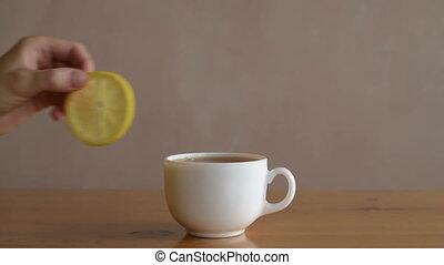 Putting lemon into a cup of tea