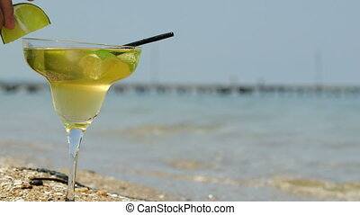 Putting lime slice on glass of cocktail by sea