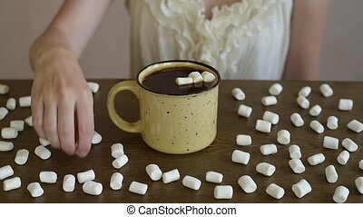 Putting marsh mallow into coffee