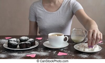 Putting marsh mallow into coffee - Woman putting marsh ...