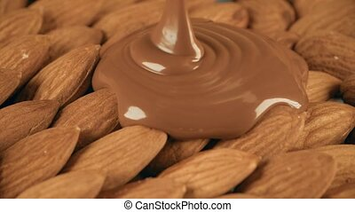 Putting melted chocolate over raw almonds - Pouring melted...