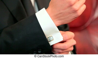 A man putting on cuff links as he gets dressed in formal wear
