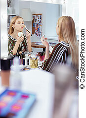Pleasant young woman looking at herself in the mirror