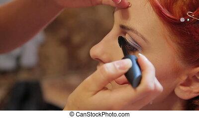 Putting on mascara - Makeup artist putting on mascara....