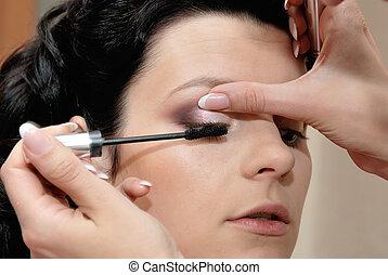 putting on mascara - Part of make-up process - applying...