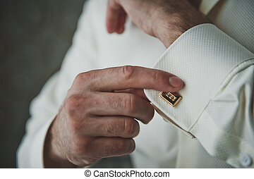 Putting on the clasps on the sleeve of a shirt 5247.
