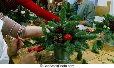 Putting ornament on Christmas tree, closeup