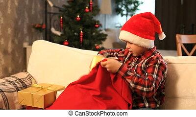Putting presents back - Boy putting presents back into...