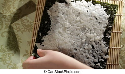 Putting rice on nori. High angle view. - Putting rice on...