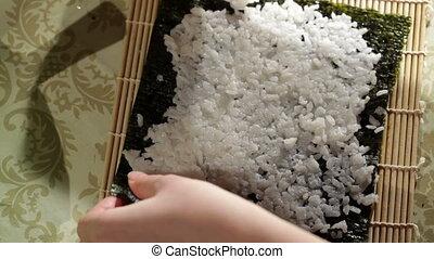 Putting rice on nori. High angle view. - Putting rice on...