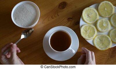Putting sugar into tea