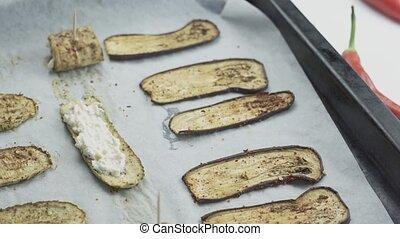 Putting tasty sour cream mixture on grilled eggplant slice. Preparing grilled eggplant rolls with feta. Grilled Eggplant Rollatini