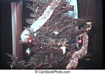 Putting Tinsel On Christmas Tree - A young family spends...