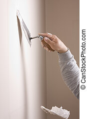 Putty Knife with Paste to Repair Wall Damage