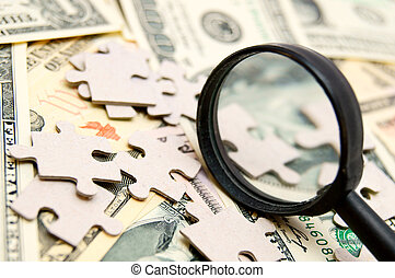 Puzzle and magnifier on money (dollars).