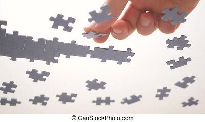 Assembling jigsaw puzzle. Pieces of a jigsaw puzzle interconnecting by male hand. Fast learning concept. Finding solution for business. Part of the whole. Assigning to learn a segment