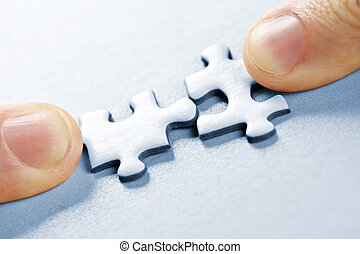 Puzzle pieces - Fingers pushing two matching puzzle pieces...