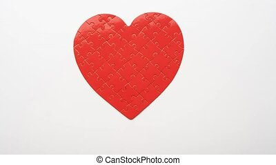 Top view of puzzle pieces forming red heart on white background, timelapse
