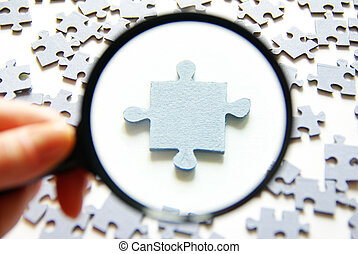 puzzle - Hand with magnifying glass and puzzle isolated on...