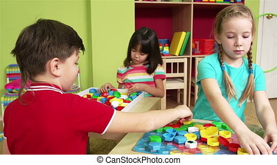 Puzzle Team - Group of preschool children making a puzzle...