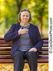 Puzzled aging woman having heart attack outdoors