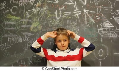 puzzled boy stands against chalkboard covered with writing
