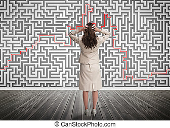Puzzled businesswoman looking at a maze on a wall