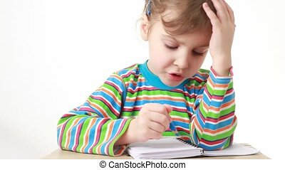 puzzled girl sitting at table with pencil and notebook