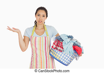 Puzzled look young woman holding laundry basket full of dirty laundry with wrinkled hands