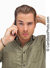 Puzzled man on the phone looking at camera
