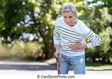 Puzzled pensioner having sudden ache in chest outdoors
