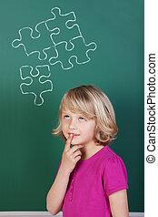 Puzzled schoolgirl in front of the blackboard