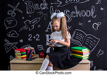 Puzzled schoolgirl sitting on the desk with books, school supplies, doing maths with calculator