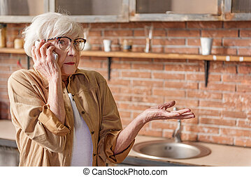 Puzzled senior lady talking on mobile phone - Portrait of...