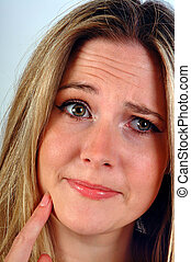 Close up of a woman with finger on chin looking puzzled.