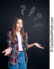Puzzled woman standing on black background