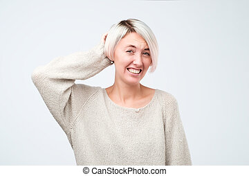 Puzzled woman with dyed short hair wearing gray sweater looking into camera having some doubts