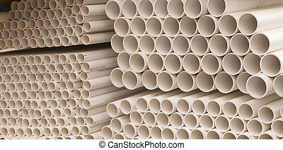 PVC Pipes - Stacks of plastic pvc plumbing pipes at a...