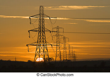 pylon sunset - Sun setting behind a row of electricity ...