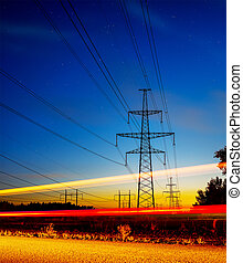 Pylons and electricity powerlines at night with traffic lights in front.
