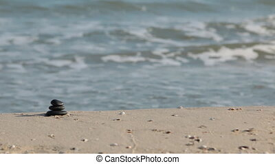 Pyramid made of black stones stands on the sand of the beach against the background of sea waves.