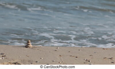 Pyramid made of white stones against the background of sea...