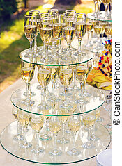 pyramid of champagne glasses during catering at party.