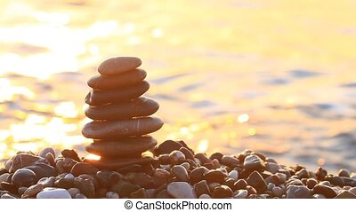 Pyramid of pebbles at sunrise on the sea